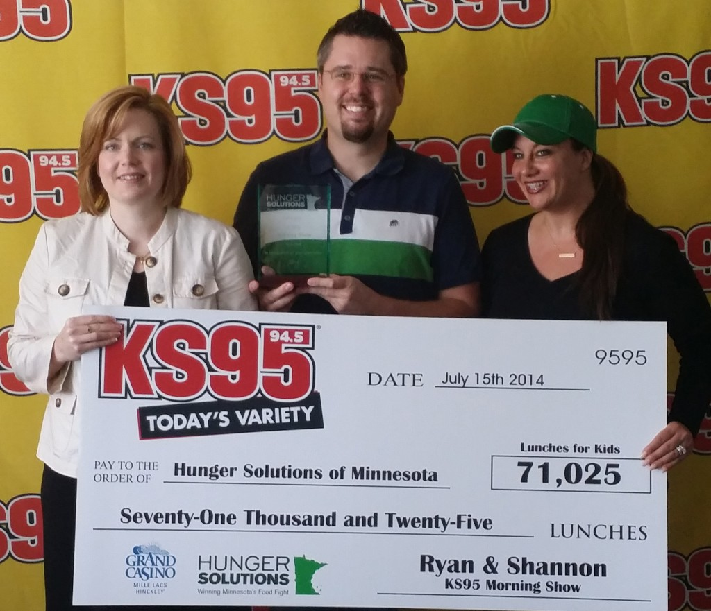Ryan and Shannon of KS95 present Jessica with a big check.