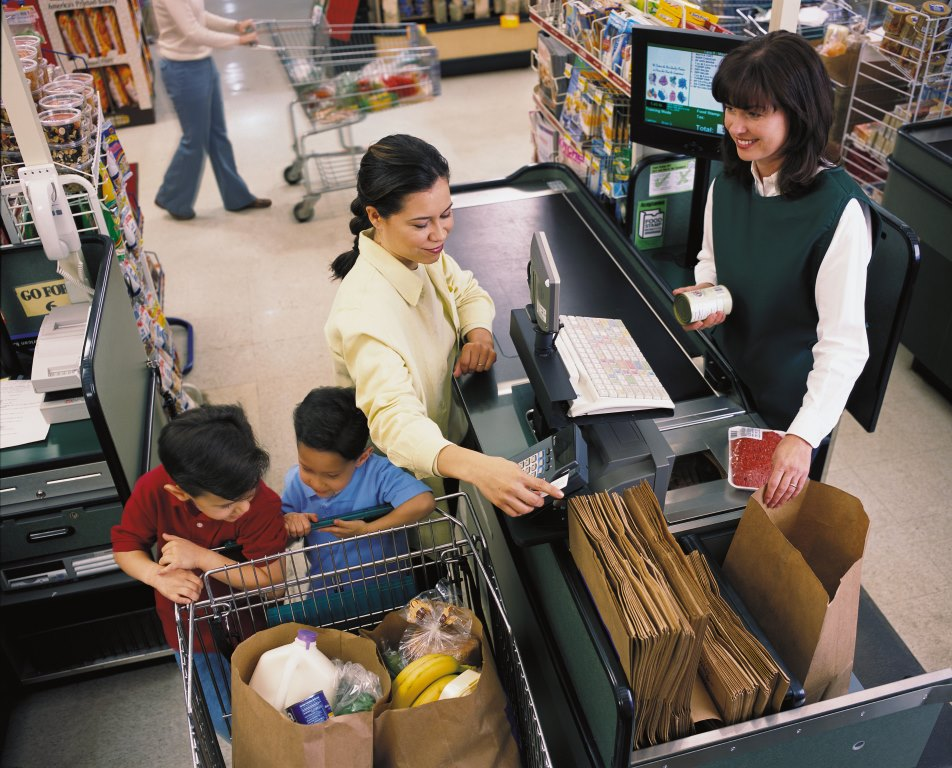 Woman at the grocery store using an EBT card to pay for groceries. A smiling cashier watches her swipe the card. Her two young sons are playing on the shopping cart in front of her. Image CC by 2.0 via flickr/USDA