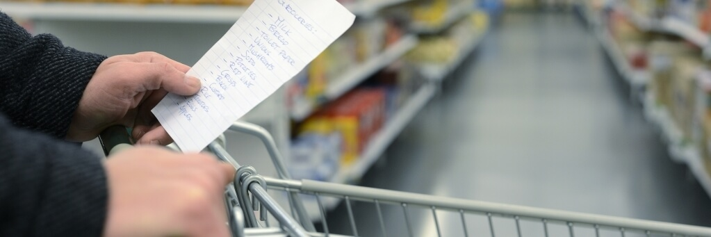 Close up of hands of a person holding a grocery list and pushing grocery cart through the store.