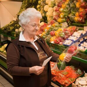 A senior woman examines a bag of tri-colored bell peppers in the produce aisle of a grocery store.