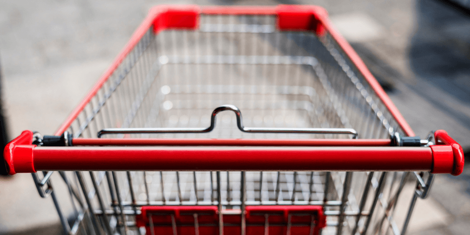 An empty wire shopping cart with red plastic handle and accents.