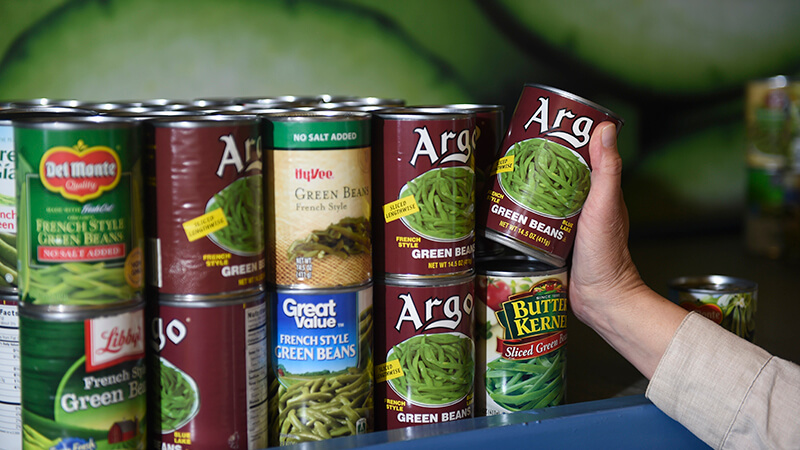 Person's hand reaches to put a can of green beans on a shelf with other green beans on a shelf. The cans all have labels from different brands, suggesting they were donated to the food shelf rather than purchased like in a store.